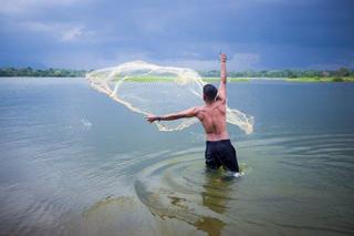Young man casting a fishing net